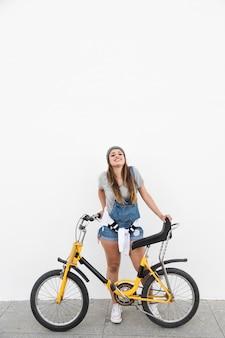 Sourire jeune femme avec vélo debout sur le trottoir