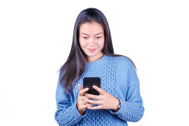 Sourire jeune fille asiatique à l'aide de smartphone faisant défiler les réseaux sociaux