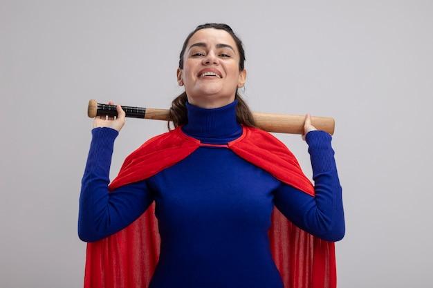 Sourire jeune fille de super-héros tenant une batte de baseball derrière le cou isolé sur blanc