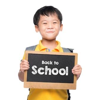 Sourire de jeune garçon asiatique tenant le tableau retour à l'école sur blanc