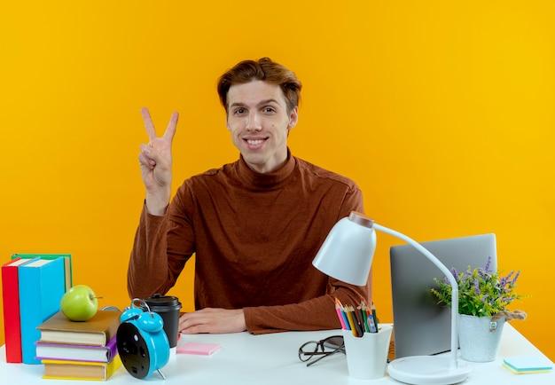 Sourire jeune garçon étudiant assis au bureau avec des outils scolaires geste de paix sur jaune