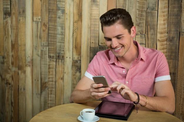Sourire jeune homme à l'aide de téléphone intelligent à table dans un café