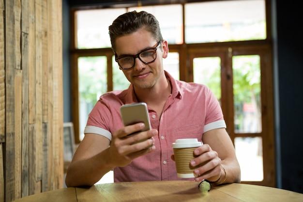 Sourire de jeune homme à l'aide de téléphone portable à table dans un café