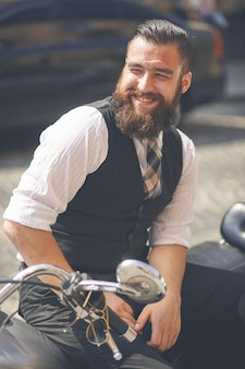 Sourire jeune homme assis sur une moto
