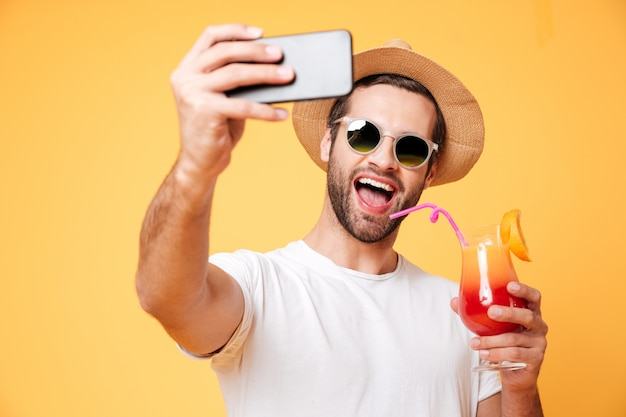 Sourire jeune homme faire selfie par téléphone tenant un cocktail.