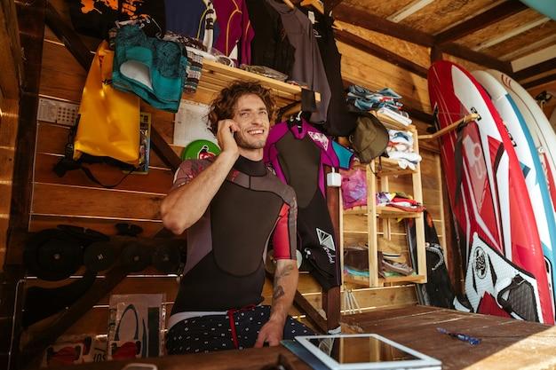 Sourire jeune homme en maillot de bain parler sur smartphone alors qu'il était assis dans la cabane de surf