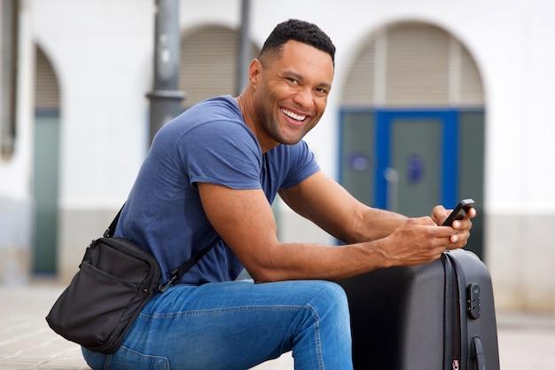 Sourire jeune homme noir assis à l'extérieur avec valise et téléphone mobile