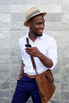 Sourire jeune homme noir avec téléphone portable et sac
