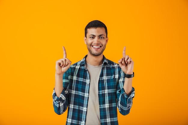 Sourire jeune homme portant une chemise à carreaux debout isolé sur un mur orange, pointant vers le haut
