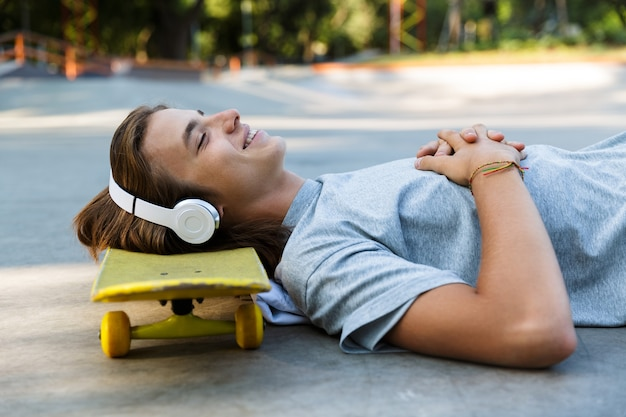 Sourire jeune mec passer du temps au skate park, écouter de la musique avec des écouteurs, pose sur planche à roulettes