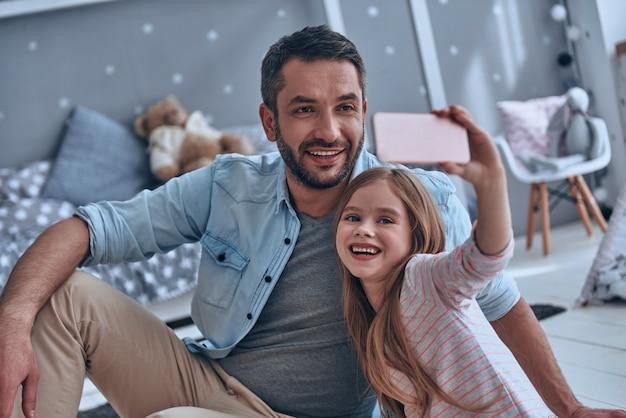 Sourire! jeune père et sa petite fille prenant un selfie assis par terre à la maison