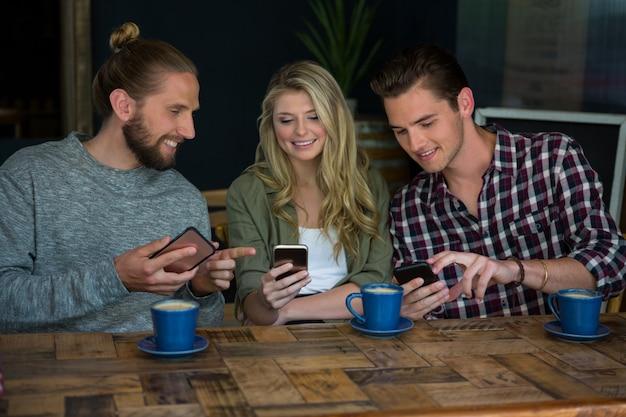 Sourire de jeunes amis à l'aide de téléphones intelligents à table au café