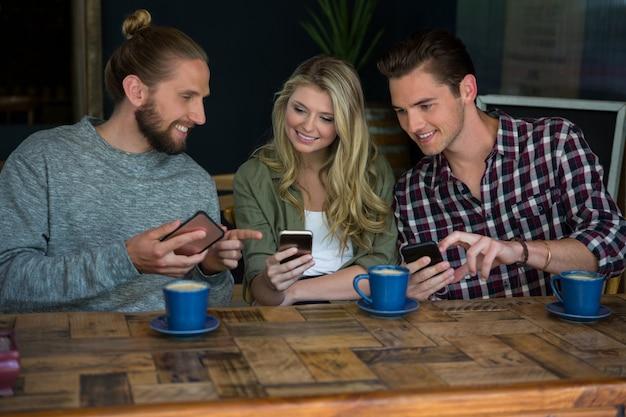 Sourire de jeunes amis à l'aide de téléphones intelligents à table à la cafétéria