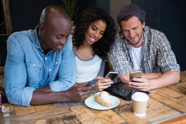 Sourire de jeunes amis à l'aide de téléphones intelligents à table dans un café