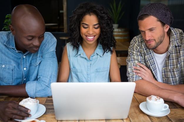 Sourire de jeunes amis utilisant un ordinateur portable à table dans un café