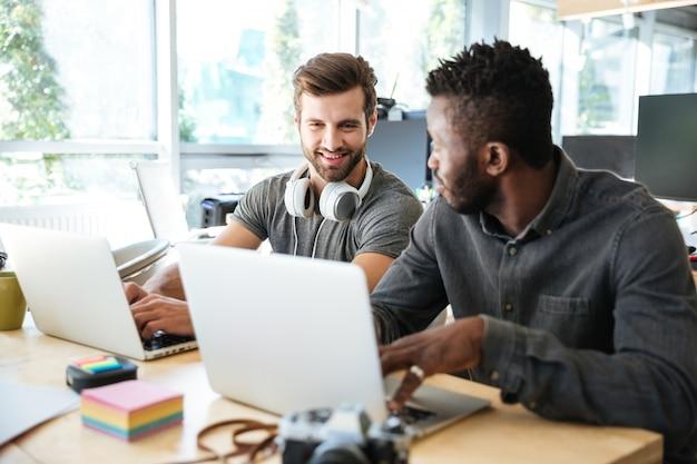 Sourire de jeunes collègues assis dans le coworking de bureau à l'aide d'un ordinateur portable