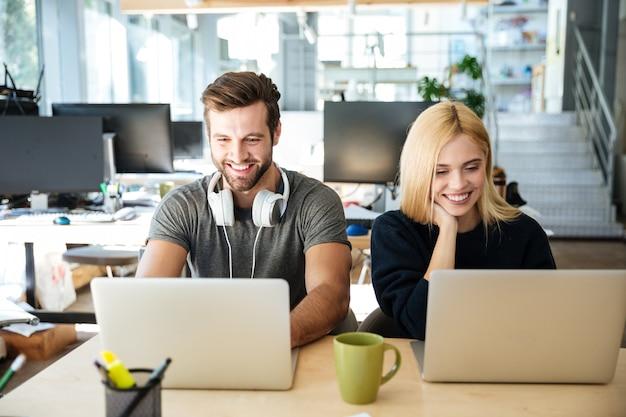 Sourire de jeunes collègues assis dans le coworking de bureau