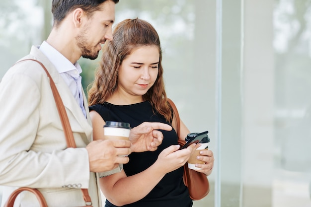 Sourire de jeunes collègues buvant du café à emporter et discutant d'une nouvelle application sur smartphone