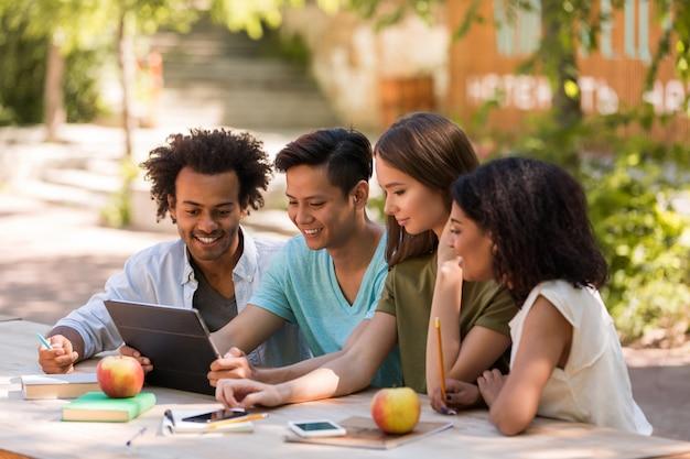 Sourire jeunes étudiants amis multiethniques à l'extérieur à l'aide de la tablette