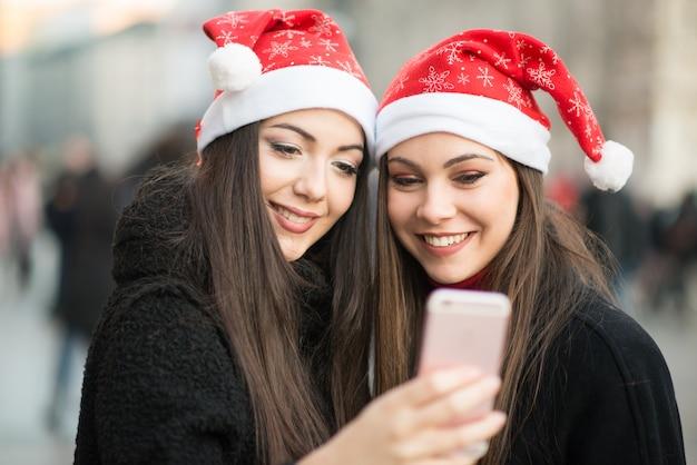 Sourire de jeunes femmes au chapeau de noël à l'aide d'un smartphone ensemble
