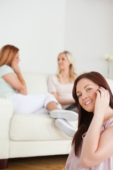 Sourire jeunes femmes discutant sur un canapé on a un téléphone