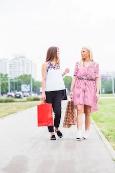 Sourire de jeunes femmes marchant avec un sac à provisions coloré