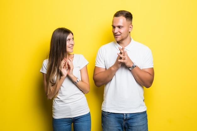 Sourire de jeunes isolés sur fond jaune serrant ensemble habillés en t-shirts blancs