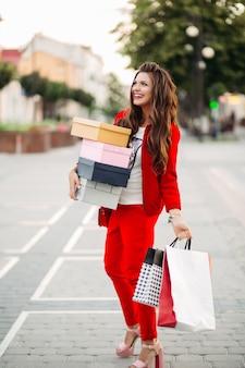 Sourire de jolie femme en costume sport chic rouge tenant des boîtes à chaussures et des sacs à provisions dans la rue.
