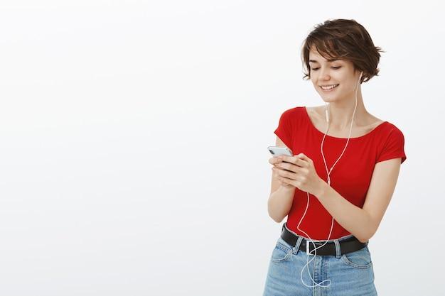 Sourire jolie femme écoutant de la musique ou un podcast, changer de chanson sur téléphone mobile