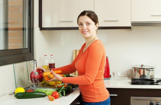 Sourire jolie femme lavant des légumes frais