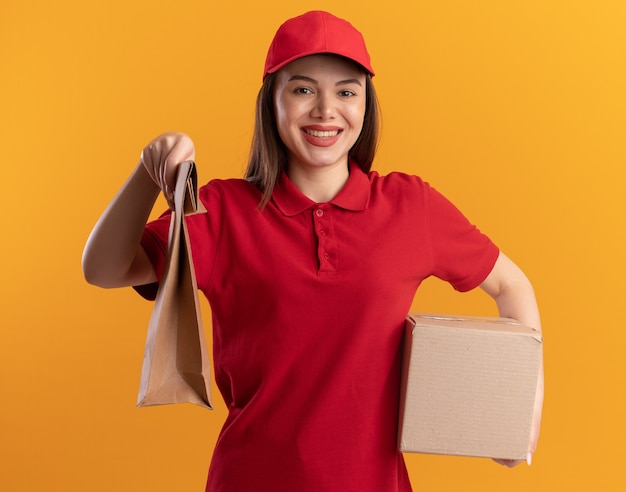 Sourire jolie femme de livraison en uniforme détient un paquet de papier et une boîte en carton sur orange