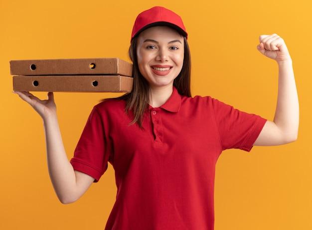Sourire jolie femme de livraison en uniforme tend les biceps et détient des boîtes à pizza sur orange