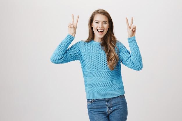 Sourire jolie femme montrer la paix v-sign