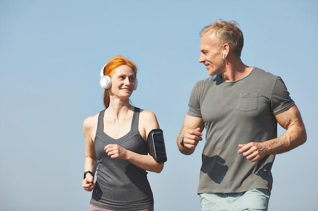 Sourire jolie femme rousse avec brassard appréciant le jogging avec petit ami le matin