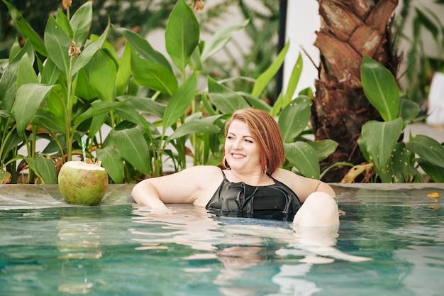 Sourire jolie femme se détendre dans la piscine de l'hôtel et boire un cocktail de noix de coco