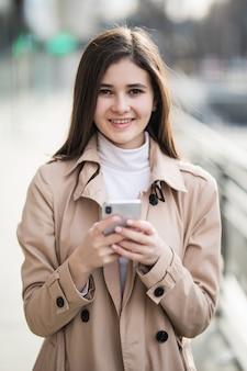 Sourire jolie jeune mannequin texte un message sur son téléphone à l'extérieur