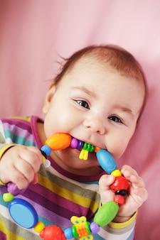 Sourire et jouer bébé avec anneau de dentition. visage gros plan.