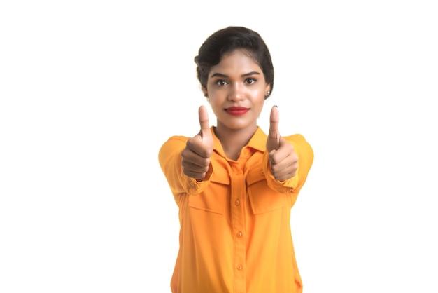 Sourire joyeuse fille montrant signe isolé sur mur blanc