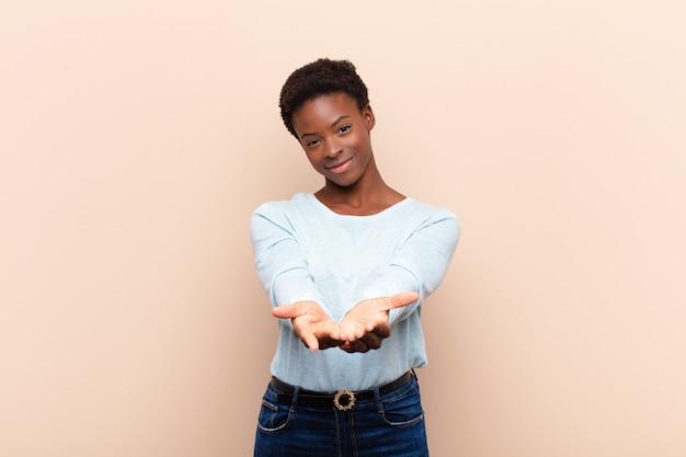 Sourire joyeusement avec un regard amical, confiant et positif, offrir et montrer un objet ou un concept