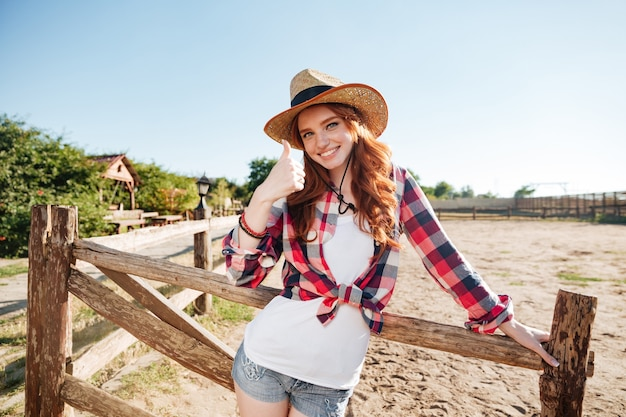Sourire joyeux cowgirl rousse au chapeau montrant le geste de pouce en l'air tout en s'appuyant sur la clôture du ranch