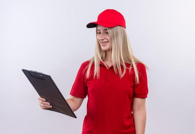 Sourire de livraison jeune fille portant un t-shirt rouge et une casquette en orthèse dentaire à la presse-papiers à portée de main sur fond blanc isolé