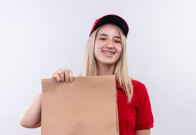 Sourire de livraison jeune fille portant un t-shirt rouge et une casquette en orthèse dentaire tenant une poche de papier sur fond blanc isolé