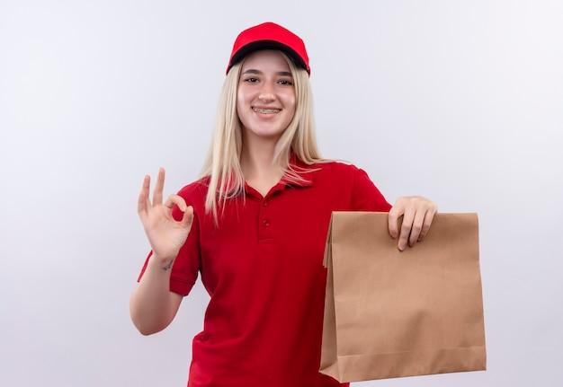 Sourire de livraison jeune fille portant un t-shirt rouge et une casquette en orthèse dentaire tenant la poche de papier montrant le geste correct sur fond blanc isolé