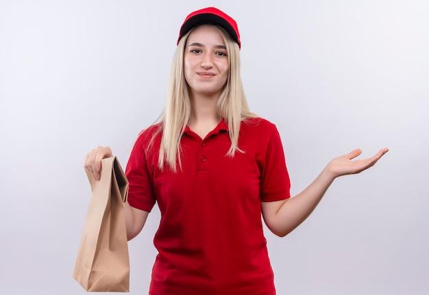 Sourire de livraison jeune fille portant un t-shirt rouge et une casquette tenant une poche de papier sur fond blanc isolé