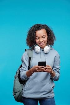 Sourire de lycée afro-américain moderne avec des cheveux bouclés textos message sur téléphone sur fond bleu