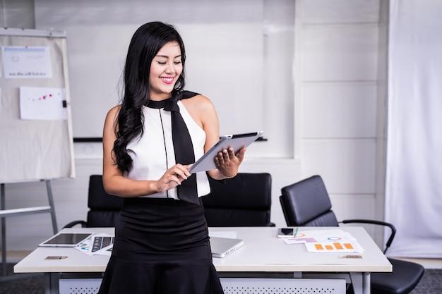 Sourire de main de femme d'affaires moderne tenant la tablette dans le bureau avec espace copie.