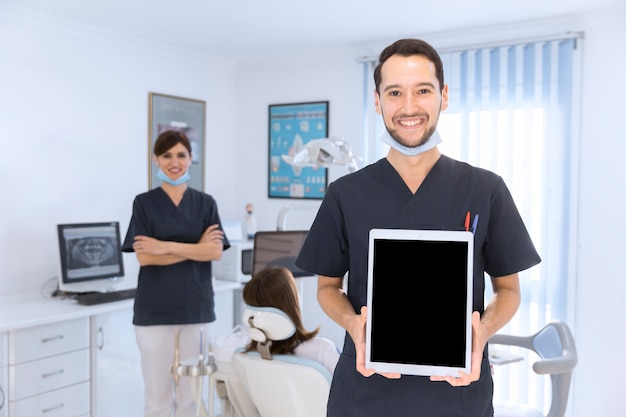 Sourire mâle dentiste montrant une tablette numérique en clinique