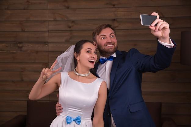 Sourire mariée et le marié faisant selfie sur téléphone mobile sur chambre en bois