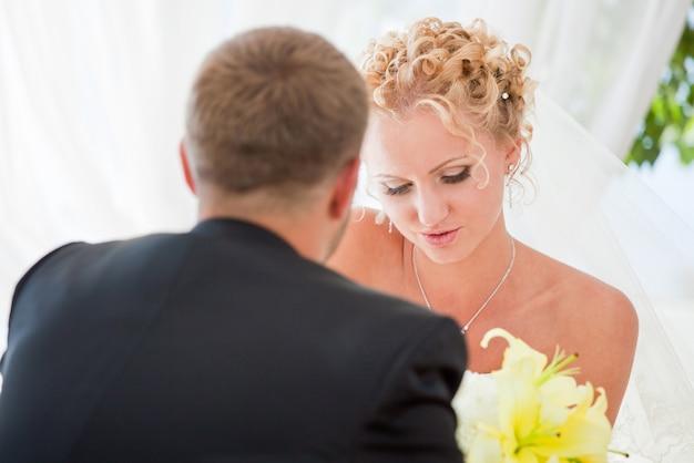 Sourire mariée et le marié sont assis au café et tenant par la main