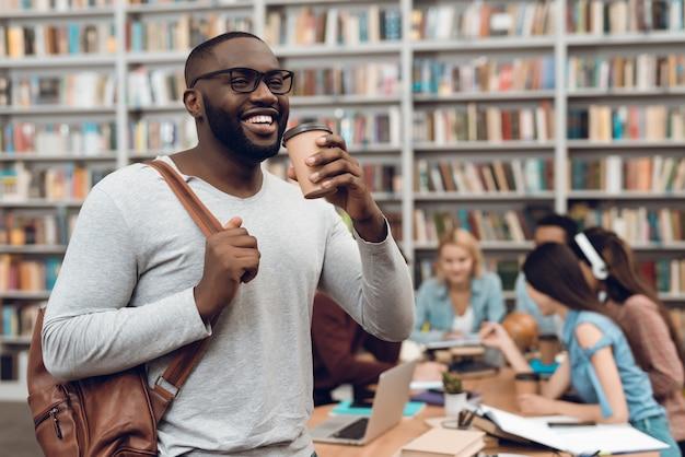 Sourire mec noir avec des notes et du café.